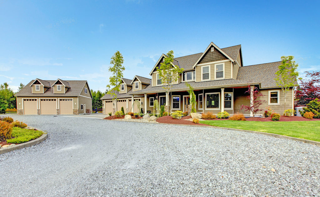 A large modern house and 3 car garage have a wide gravel driveway so that fire trucks can maneuver easily