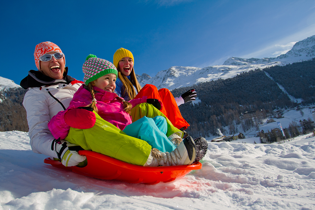 Mom and 2 young daughters excitedly sledding down a snowy mountain.