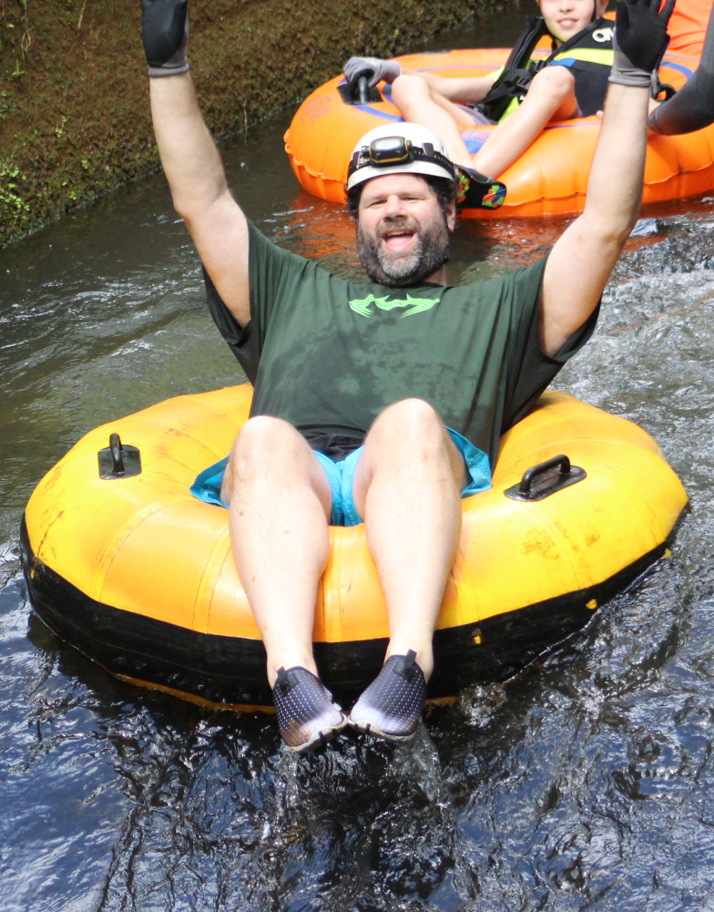 Man excitedly mountain tubing down a river.
