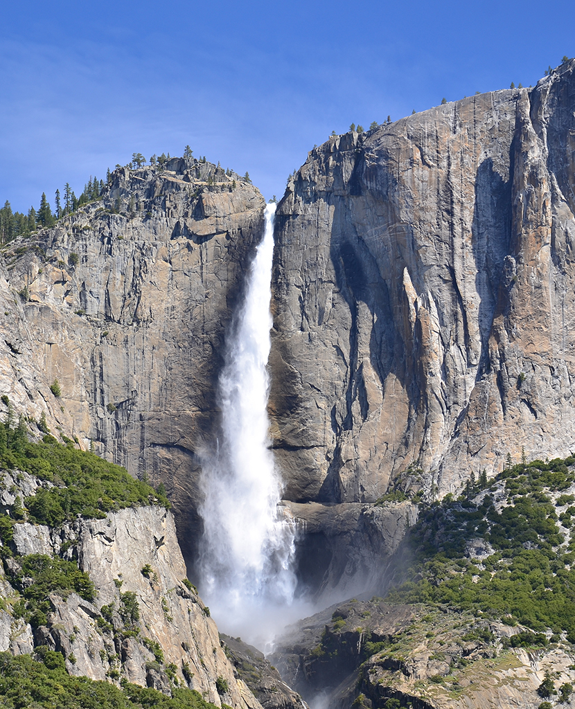 Striking image of Yosemite Falls rushing from the top of the cliff into the valley.