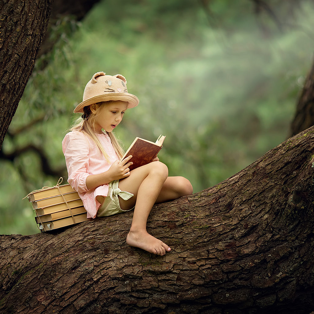 Girl reading books in a tree